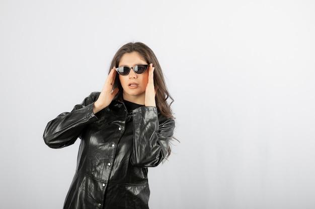 Giovane donna in cappotto nero con gli occhiali e in posa.