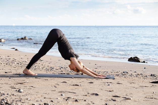 Young woman in black doing yoga on asian sand beach