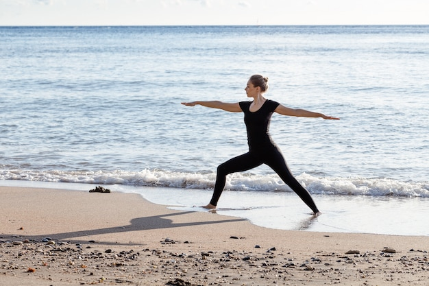Young woman in black doing yoga on sand beach