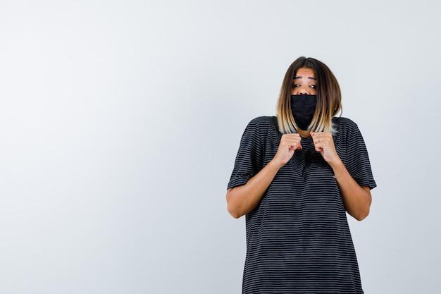 Giovane donna in abito nero, maschera nera che stringe i pugni e sembra spaventata, vista frontale.