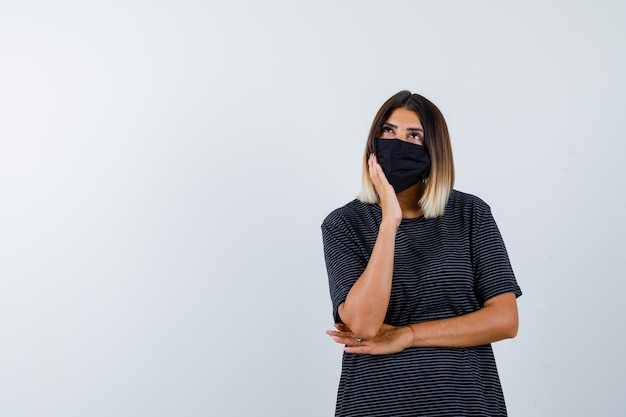 Giovane donna in abito nero, maschera nera che appoggia la guancia sul palmo, pensando a qualcosa e guardando pensieroso, vista frontale.