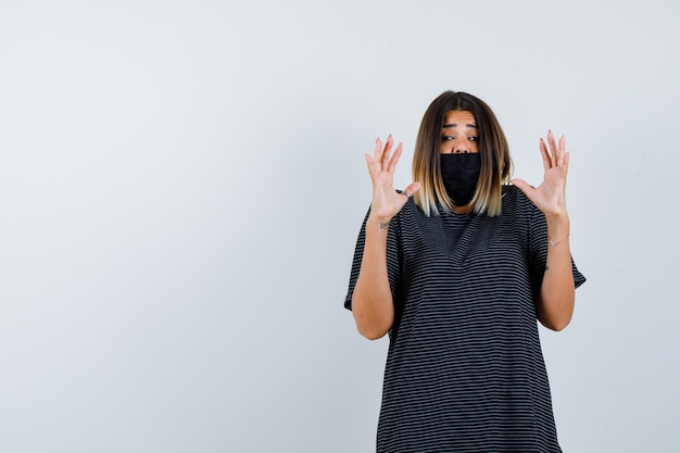 Giovane donna in abito nero, maschera nera che alza i palmi in gesto di resa e sembra spaventata, vista frontale.