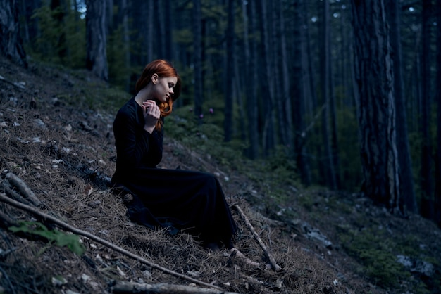 Young woman in a black dress in a dark gloomy forest, drama