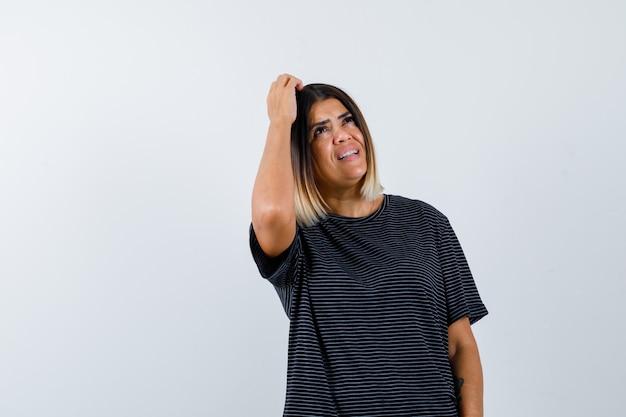 Giovane donna in abito nero che tiene una mano sulla testa, pensando a qualcosa e guardando pensieroso, vista frontale.