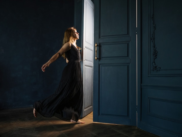 A young woman in a black dress opens a door from which light is pouring