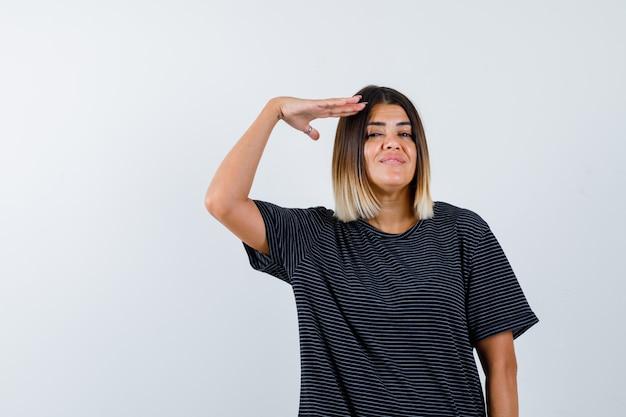 Giovane donna in abito nero che mostra gesto di saluto e guardando fiducioso, vista frontale.