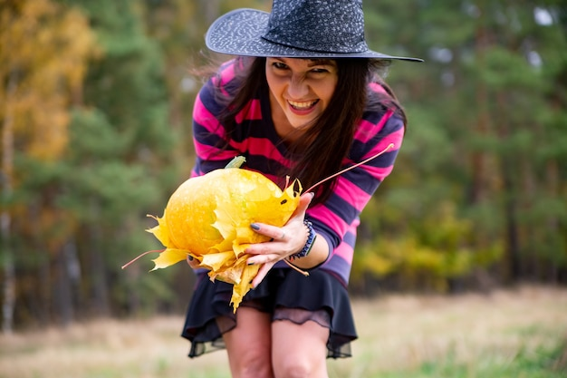Young woman in black dress with witch hat and orange pumpkin placed around in the forest, halloween concept. horror