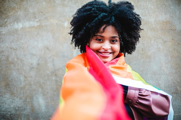 Young woman of black ethnicity wearing the rainbow colored peace flag.