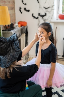 Young woman in black halloween attire applying makeup on face of little girl