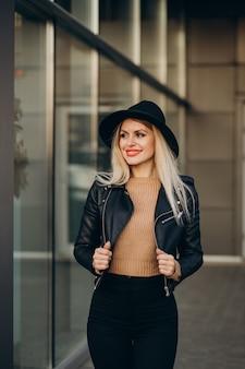 Giovane donna con cappello nero che cammina fuori dalla strada