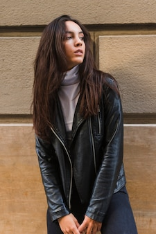 Young woman in black leather jacket standing against wall looking away