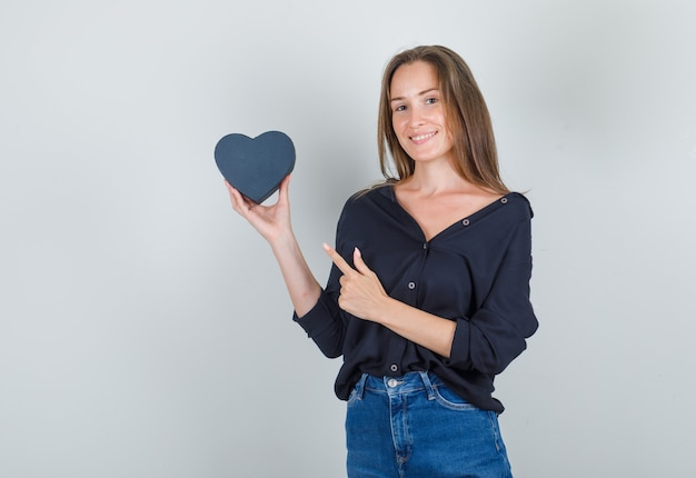 Young woman in black shirt, jeans shorts pointing finger at gift box and looking joyful