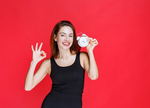 Young woman in black singlet holding an alarm clock and showing positive hand sign