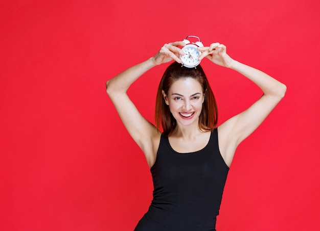 Young woman in black singlet holding an alarm clock