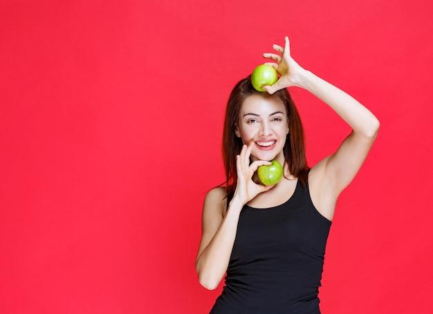 Giovane donna in canottiera nera con mele verdi sopra la testa