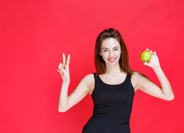 Giovane donna in canottiera nera che tiene in mano mele verdi e mostra il segno della pace