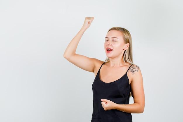 Giovane donna in canottiera nera alzando la mano con il pugno chiuso e guardando felice