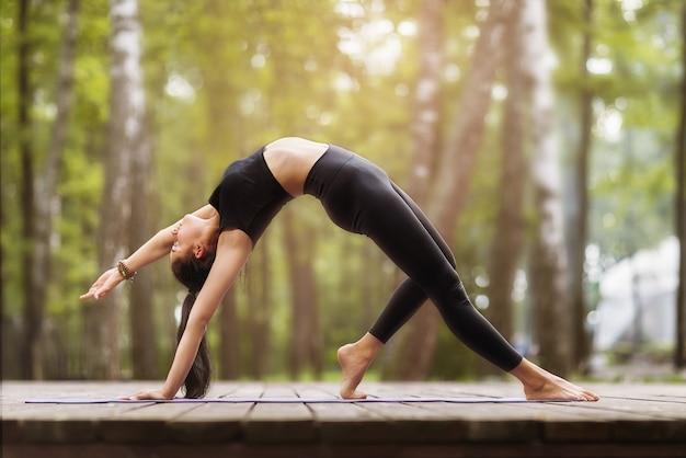 Young woman in black sportswear practicing yoga performs kamatkarasana exercise or dancing dog pose