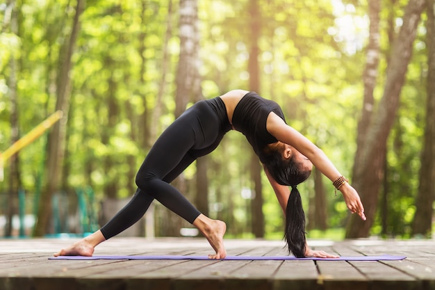 Young woman in black sportswear practicing yoga performs in the park the exercise kamatkarasana dancing dog pose