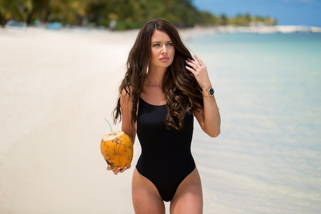 Young woman in black swimsuit with coconut cocktail on the beach