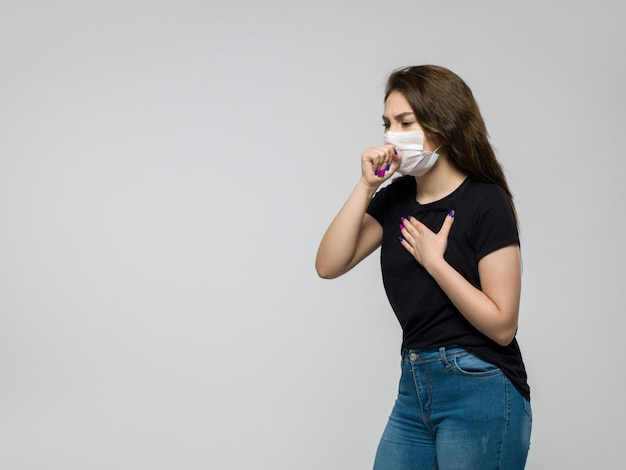 Young woman in black t-shirt and blue jeans with white sterile mask coughing