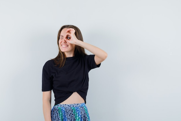 Young woman in black t-shirt and blue skirt showing ok sign on eye and looking happy
