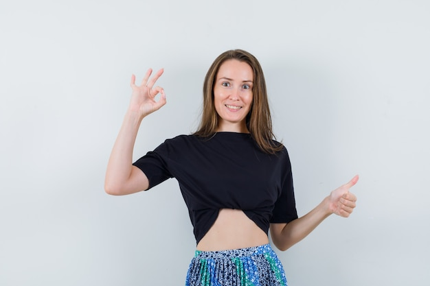 Young woman in black t-shirt and blue skirt showing ok and thumb up sign and looking happy