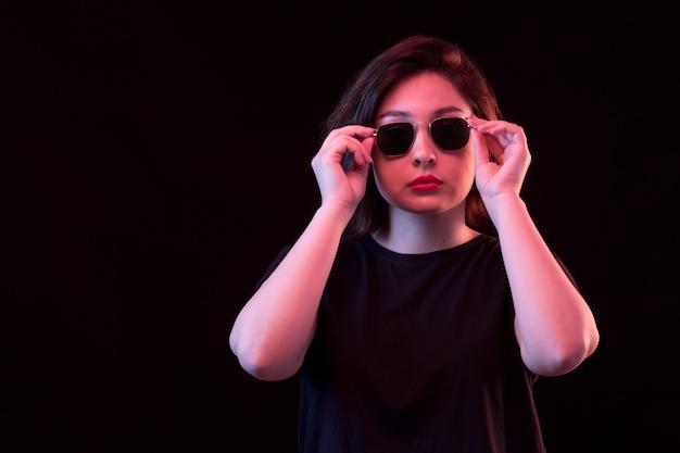 Giovane donna in maglietta nera e occhiali da sole in posa sulla parete nera