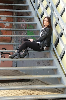 Young woman in black tight denim, white shirt and leather jacket sits on metal stairs