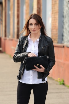 Young woman in black tight denim, white shirt and leather jacket on the street