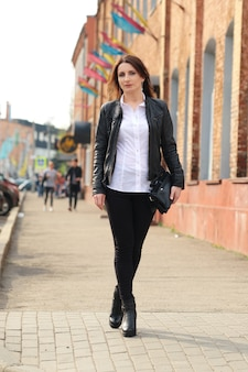 Young woman in black tight denim, white shirt and leather jacket walks along the street