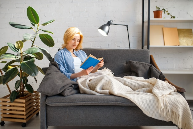 Young woman under a blanket reading a book on cozy yellow couch, living room in white tones