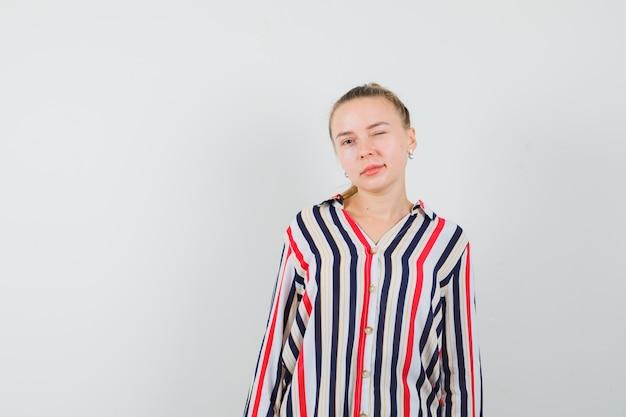 Молодая женщина моргает и позирует в полосатой блузке и выглядит уверенно