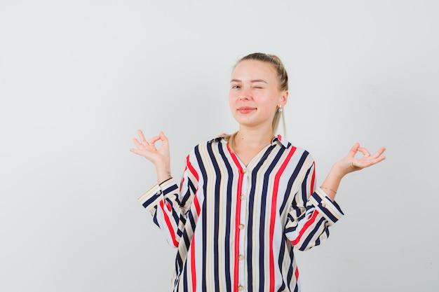 Молодая женщина моргает и показывает жест мира в полосатой блузке и выглядит счастливой