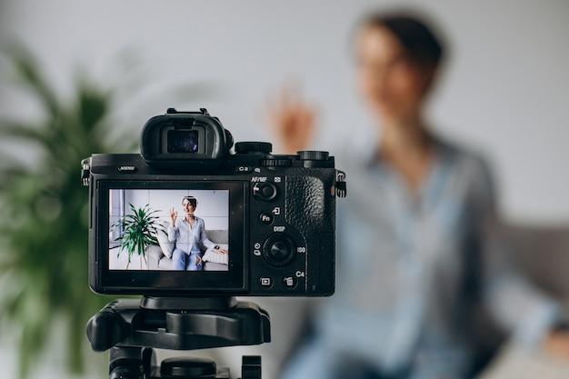 Blogger di giovane donna che registra video sulla fotocamera