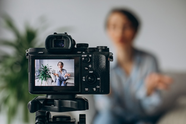 Young woman blogger recording video on camera