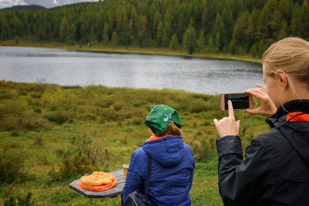 若い女性ブロガーは、山の湖に対して後ろから彼女の友人の写真を撮ります。針葉樹林に覆われた美しい山々のテーブルでの観光ピクニック。