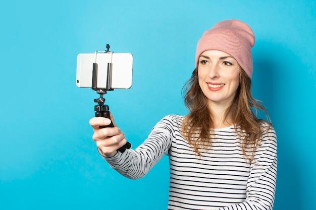 若い女性ブロガーは青い表面の電話で自分の写真を撮ります