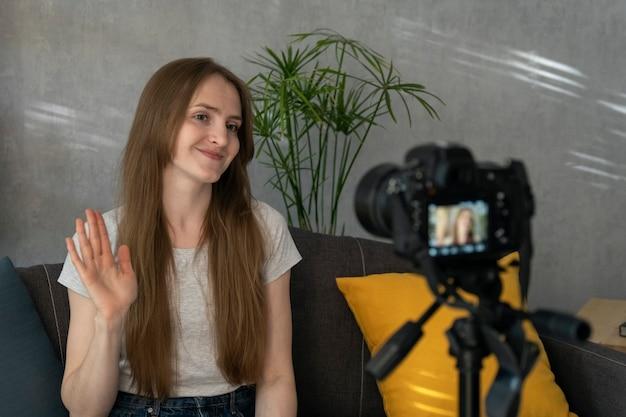 젊은 여성 블로거는 카메라에 자신의 비디오를 찍고 손을 흔듭니다. 블로깅을 위해 자신을 촬영하는 아름다운 소녀