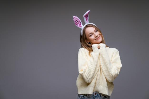 Молодая женщина, блондинка, в белых кроличьих ушах и в легком свитере на серой стене