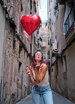 路上で屋外で赤いハート型の風船を持ってカメラにエアキスを吹く若い女性。愛とバレンタインデーのコンセプト。