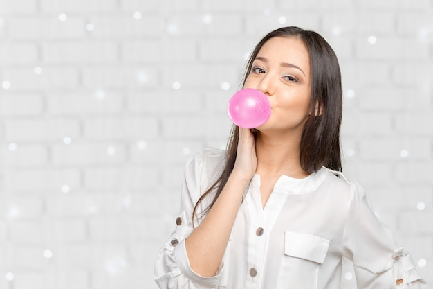 Young woman blowing bubblegum
