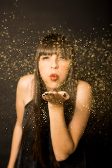 Young woman blowing confetti from hand