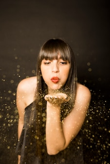 Young woman blowing confetti from palm