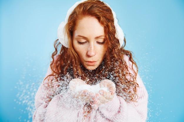 Giovane donna che soffia neve finta in studio shot