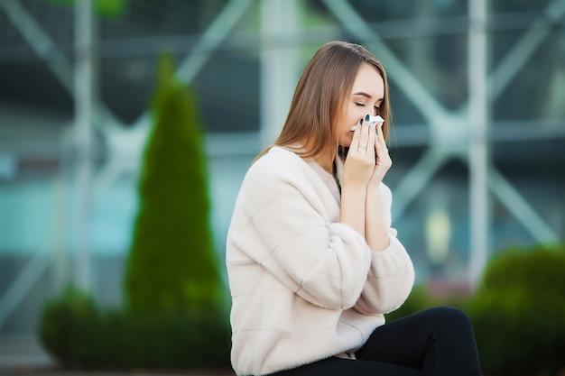 Молодая женщина, сморкающаяся в парке.