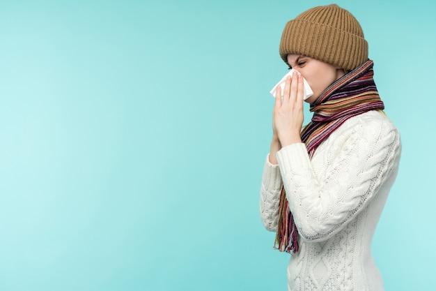 Молодая женщина сморкается в ткани на синем фоне