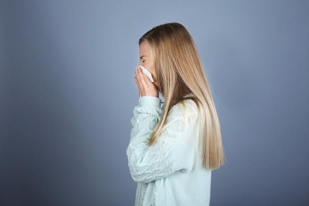 Молодая женщина сморкается на ткани на цветном фоне