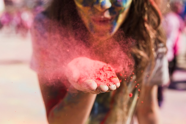 Young woman blowing the red holi color toward camera