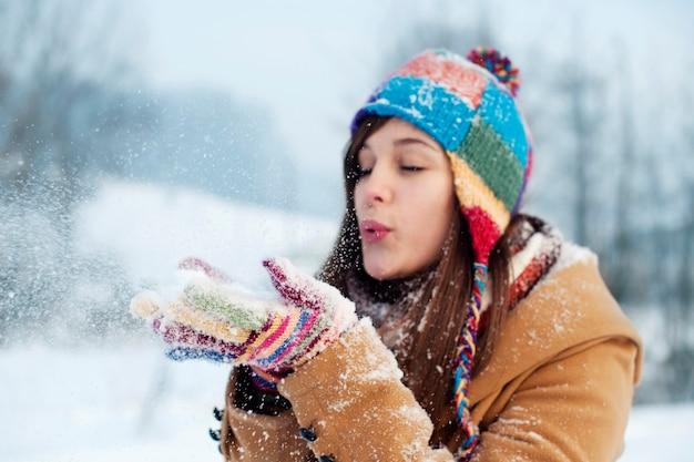 離れて雪を吹く若い女性
